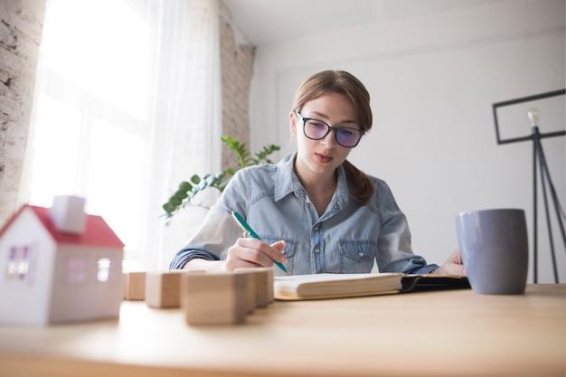 Porträt eines weiblichen architektenschreibens auf buch am arbeitsplatz
