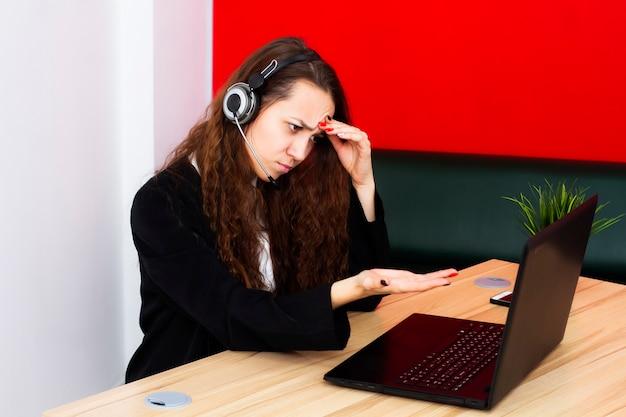 Porträt eines weiblichen betreibers an einem computer in einem büro.