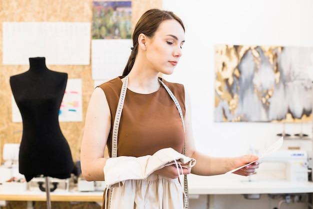 Porträt eines weiblichen designers mit gewebe- und modeskizze
