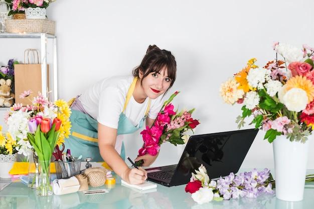 Porträt eines weiblichen floristen mit den blumen, die auf notizblock schreiben