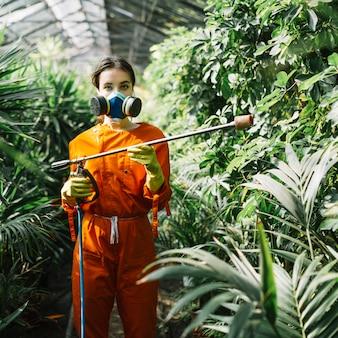 Porträt eines weiblichen gärtners mit verschmutzungsmaske, das insektizid auf pflanzen sprüht