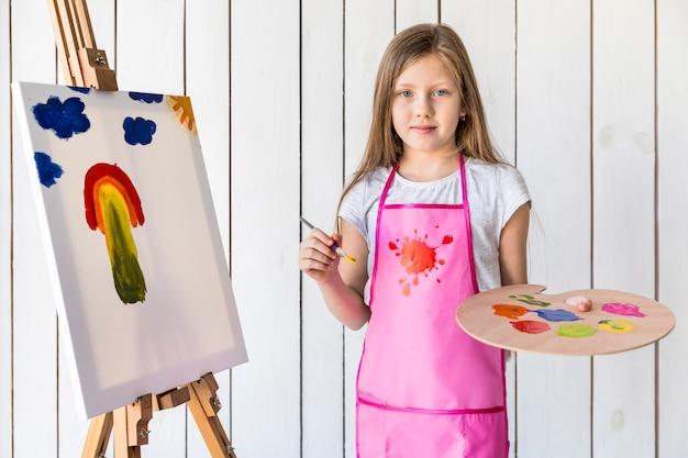 Porträt eines weiblichen künstlers, der pinsel und palette stehen gegen weiße hölzerne wand hält