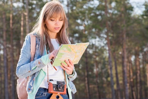 Porträt eines weiblichen reisenden, der auf karte im wald sucht