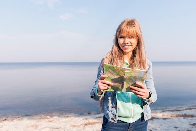 Porträt eines weiblichen reisenden, der die karte in der hand betrachtet die kamera steht nahe dem meer hält