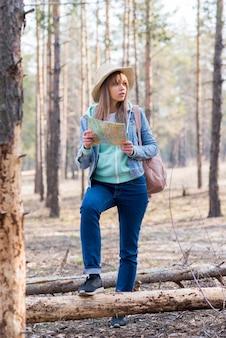 Porträt eines weiblichen reisenden, der im wald mit karte steht