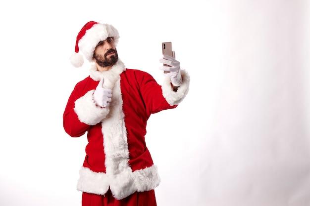 Porträt eines weihnachtsmannes, der ein selfie mit einem smartphone auf weißem hintergrund macht