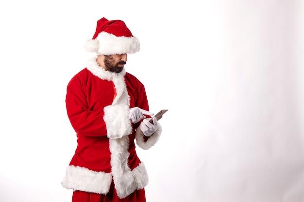 Porträt eines weihnachtsmannes mit einem smartphone auf weißem hintergrund