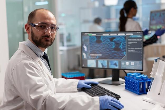 Porträt eines wissenschaftlers, der die kamera betrachtet, die in einem modern ausgestatteten labor sitzt. wissenschaftler arzt untersucht die virusentwicklung mit high-tech-eingabe auf computerchemie-tools für die wissenschaftliche forschung