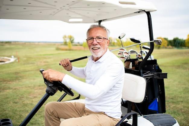 Porträt eines wohlhabenden älteren mannes, der golfauto in die grüne zone fährt, um weiter zu spielen.