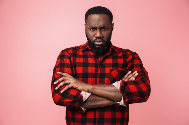 Porträt eines wütenden afrikanischen mannes, der ein kariertes hemd trägt, der isoliert über einer rosa wand steht, die arme verschränkt