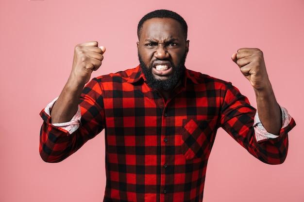 Porträt eines wütenden afrikanischen mannes, der ein kariertes hemd trägt, der isoliert über einer rosa wand steht und schreit