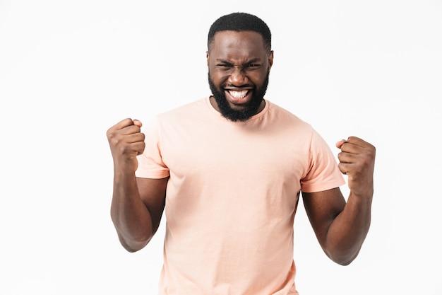 Porträt eines wütenden afrikanischen mannes, der ein t-shirt trägt, das isoliert über einer weißen wand steht?