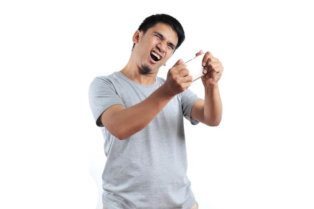 Porträt eines wütenden asiatischen mannes mit grauem t-shirt, der auf dem smartphone auf weißem hintergrund wütend wird