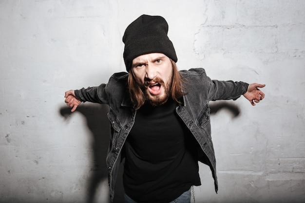 Porträt eines wütenden hipster-typen, der auf der vorderseite schreit, isoliert über der wand?