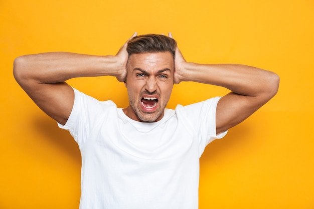 Porträt eines wütenden kerls der 30er jahre im weißen t-shirt, der schreit und den kopf greift, isoliert auf gelb