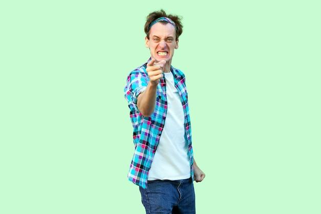 Porträt eines wütenden, nervösen jungen mannes in lässigem blau kariertem hemd und stirnband, der steht, die zähne zusammenbeißt, die kamera beschuldigt und betrachtet. indoor-studioaufnahme, isoliert auf hellgrünem hintergrund.