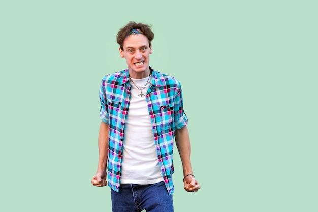Porträt eines wütenden, nervösen jungen mannes in lässigem blau kariertem hemdstirnband, das die zähne zusammenbeißt und die kamera mit wütendem gesicht betrachtet. indoor-studioaufnahme, isoliert auf hellgrünem hintergrund.