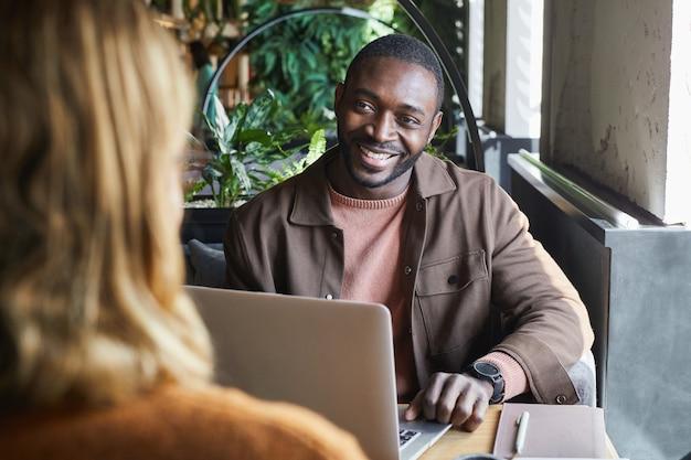 Porträt eines zeitgenössischen afroamerikanischen mannes, der den partner während eines geschäftstreffens am café-tisch anlächelt, platz kopieren