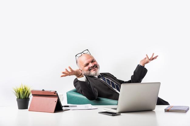 Porträt eines zufriedenen älteren indischen asiatischen geschäftsmannes, der am arbeitsplatz vor dem computer sitzt und beim entspannen in die kamera schaut. alte berufsmannfüße auf schreibtisch