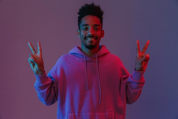 Porträt eines zufriedenen afroamerikanischen mannes in buntem hoodie, der lächelt und frieden zeigt, singen isoliert über violetter wand