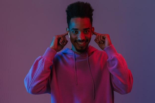 Porträt eines zufriedenen afroamerikanischen mannes in einem bunten hoodie, der musik mit ohrstöpseln hört, die über einer violetten wand isoliert sind?