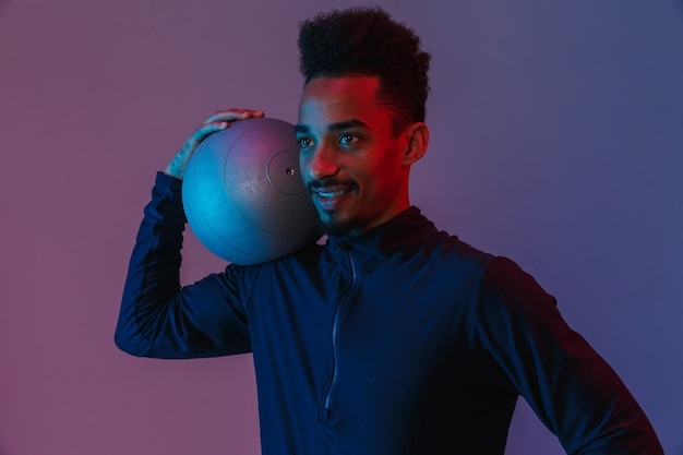 Porträt eines zufriedenen afroamerikanischen mannes in sportkleidung, der mit ball über violette wand isoliert posiert