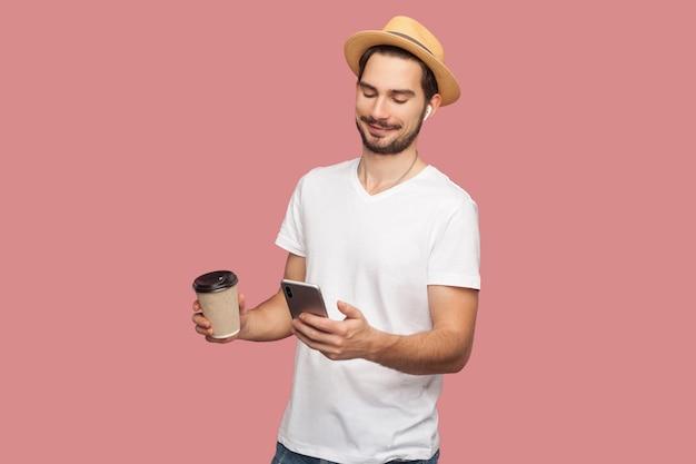 Porträt eines zufriedenen, gutaussehenden, bärtigen jungen hipster-blogger-mannes in weißem hemd und lässigem hut, der mit kaffee steht und am telefon plaudert. innen, isoliert, studioaufnahme, rosa hintergrund