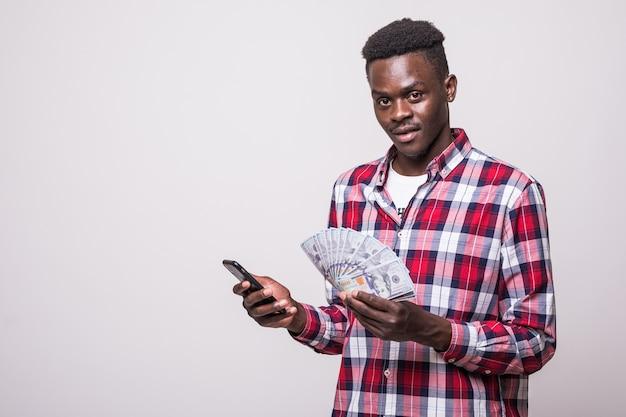 Porträt eines zufriedenen jungen afrikanischen mannes gekleidet im karierten hemd, das handy und bündel geldbanknoten isoliert hält