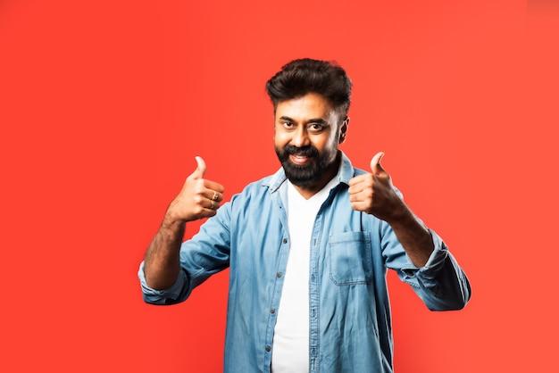 Porträt eines zufriedenen jungen indischen mannes, der erfolg auf rot feiert