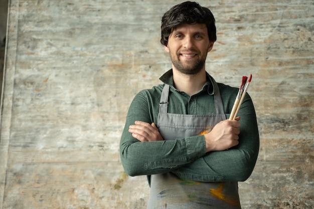 Porträt eines zufriedenen jungen männlichen künstlers, der mit einem pinsel in der hand die arme verschränkt