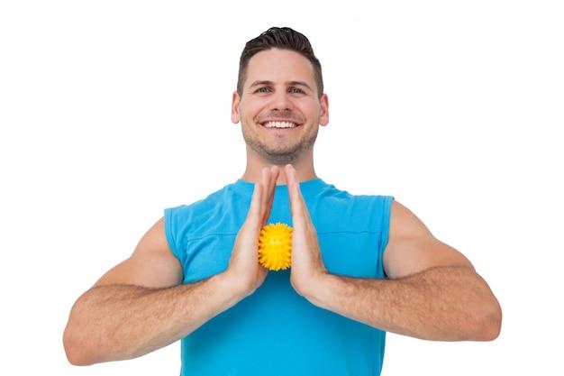 Porträt eines zufriedenen jungen mannes, der druckball hält