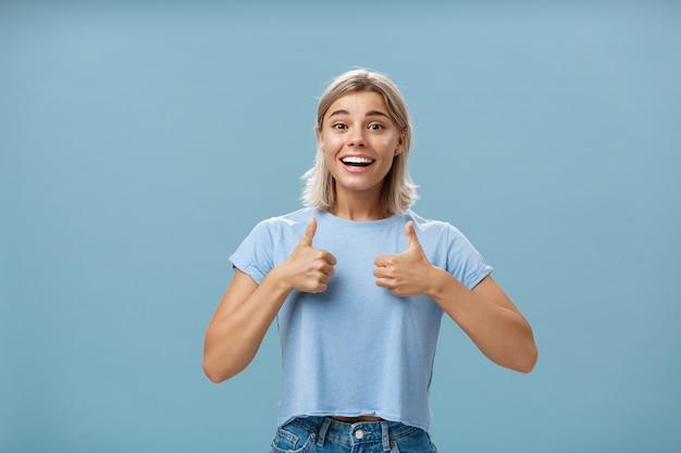 Porträt eines zufriedenen und faszinierten glücklichen mädchens, das daumen hoch zeigt und breit lächelt, unterstützend und fröhlich ist