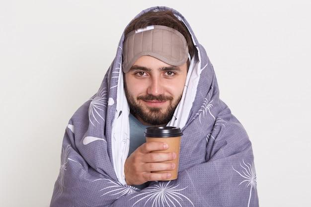 Porträt eines zufriedenen unrasierten mannes mit kaffee oder tee in den händen, bärtiger kerl, der gut gelaunt ist und heißes getränk am morgen genießt