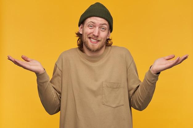Porträt eines zweifelhaften, verwirrten mannes mit blonden haaren und bart. trägt grüne mütze und beigen pullover. achselzucken mit erhobenen händen und schiefem gesicht. isoliert über gelbe wand