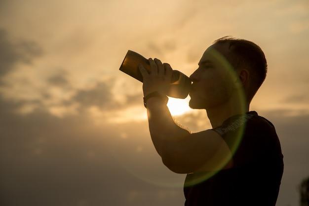 Porträt, entwurf eines sportlichen jungen kaukasischen kerls in einem schwarzen t-shirt und trinkwasser der schwarzen kurzen hosen