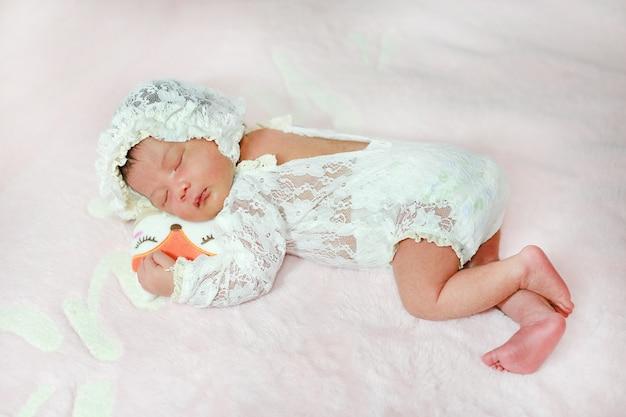 Porträt entzückend des kleinen asiatischen neugeborenenbabys, das auf flauschigem weichem bett schläft.