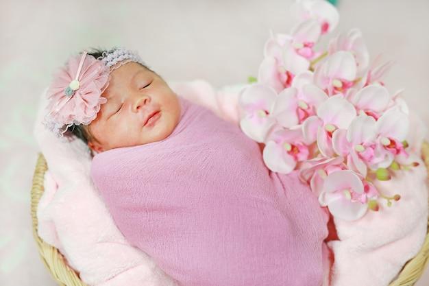Porträt entzückend des kleinen asiatischen neugeborenenbabys, das auf flauschigem weichem handtuch im korb schläft