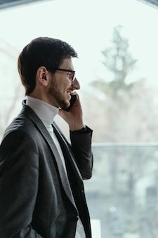 Porträt erfolgreicher geschäftsmann, der auf dem smartphone spricht