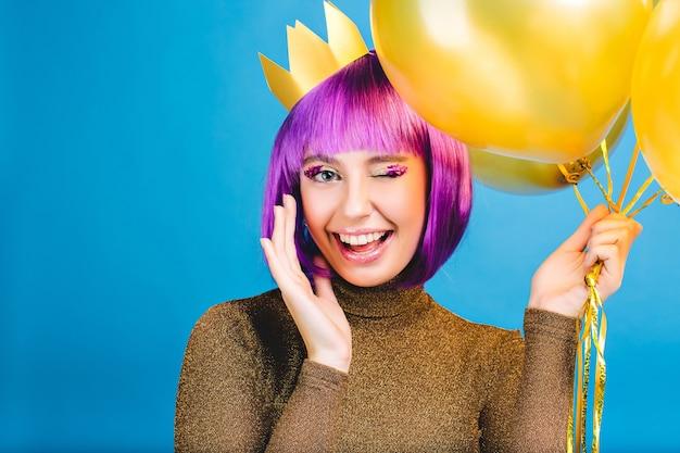 Porträt erstaunliche junge frau, die karneval feiert, große party. schneiden sie lila haare, rosa lametta make-up, goldene krone, luftballons. urlaubsstimmung, glück, positivität ausdrücken.
