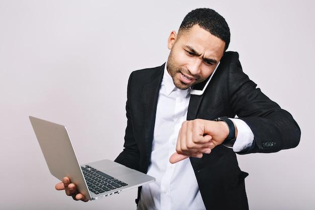 Porträt fleißiger beschäftigter junger mann im weißen hemd, in der schwarzen jacke, die am telefon spricht und auf uhr schaut. stilvoller geschäftsmann, der mit laptop arbeitet, zeit für arbeit, treffen.