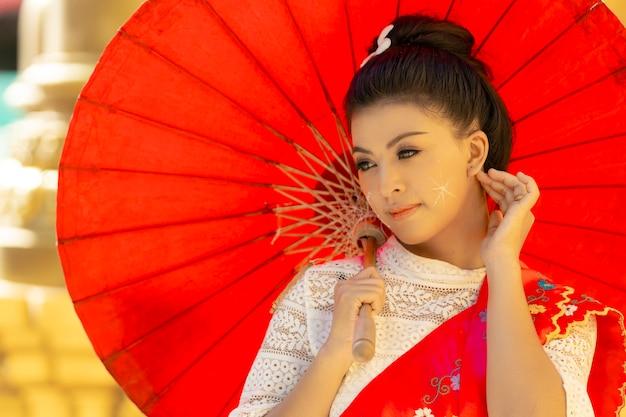 Porträt frau in burmesischer tracht trägt einen roten regenschirm.