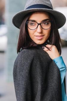 Porträt freudige junge modische frau mit brünettem haar in den schwarzen gläsern, die auf straße in der stadt gehen. grauer mantel, hut, luxuriöser lebensstil, elegante aussicht