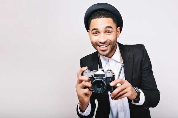 Porträt freudiger erfolgreicher kerl im anzug, hut, der spaß mit kamera hat. glücklicher tourist, fotograf, stilvoller blick, reisen, lächeln, aufgeregt, isoliert.