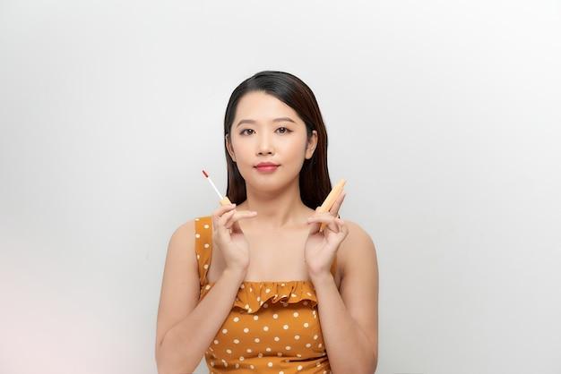 Porträt fröhliche attraktive junge frau posiert mit rosa lippenstift und wimperntusche pinsel in den händen und lächeln isolierten weißen hintergrund.