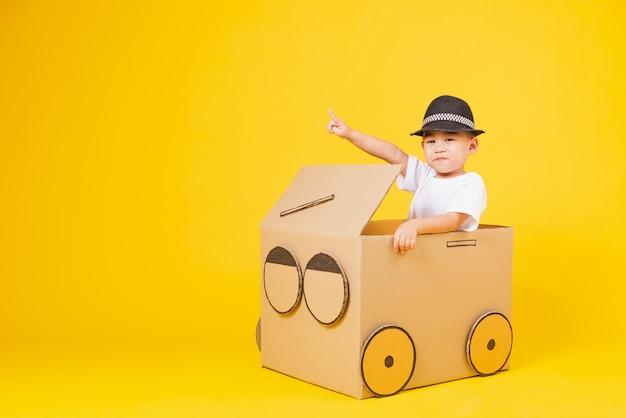 Porträt glücklich asiatische kleine kinder junge lächeln so glücklich autofahren kreativ durch pappe und zeigefinger