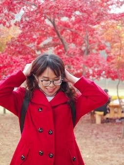 Porträt glückliche brillen asiatische frau im roten mantel berühren haare im bunten herbst bäume garten park
