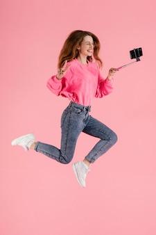 Porträt glückliche frau, die mit selfie-stock springt
