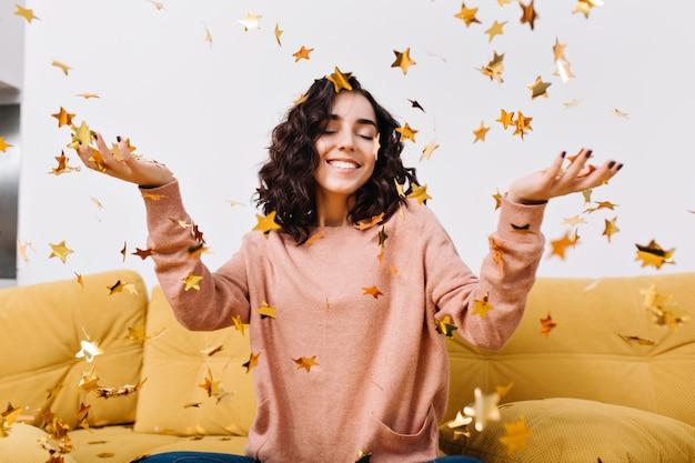 Porträt glückliche junge frau chillen, spaß haben, mit geschlossenen augen zwischen fallenden goldenen lametta auf couch in der modernen wohnung lächelnd. entspannen sie sich, glück, wahre positive emotionen