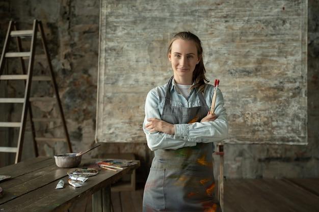 Porträt glückliche künstlerin, die eine schürze trägt, die kamera betrachtet und lächelt, während sie in ihrem kunststudio steht