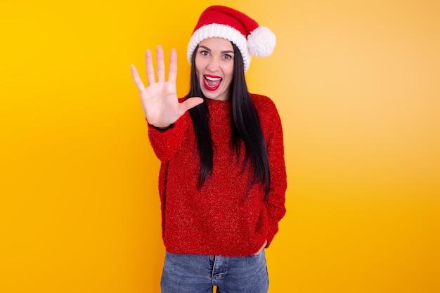 Porträt glückliche, lächelnde frau, die weihnachtsmannmütze trägt und fünf finger zeigt.
